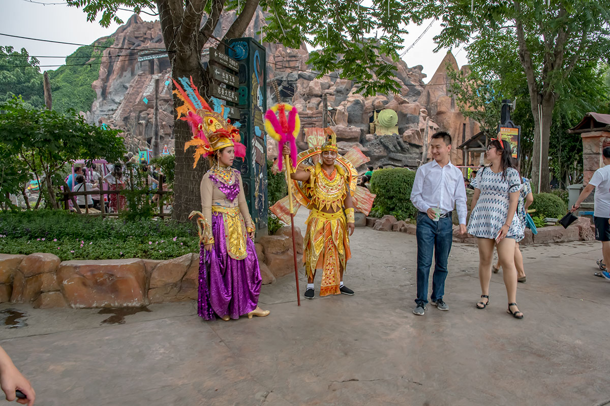 На фоне красочных декораций сценической площадки парка Happy Valley наблюдали рекламную акцию актеров в замысловатых одеяниях.