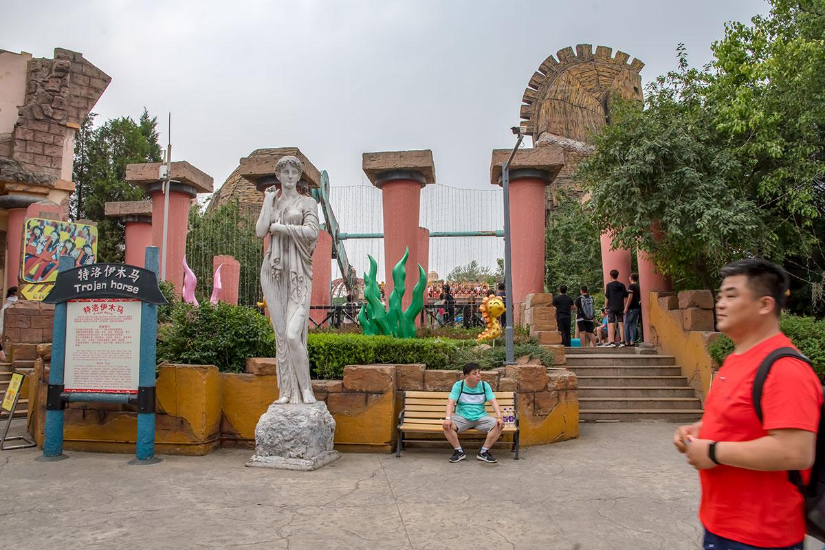 Позади копии неизвестной женской статуи в парке Happy Valley – шеренга колонн, выглядящих необычно, словно перевернутые.