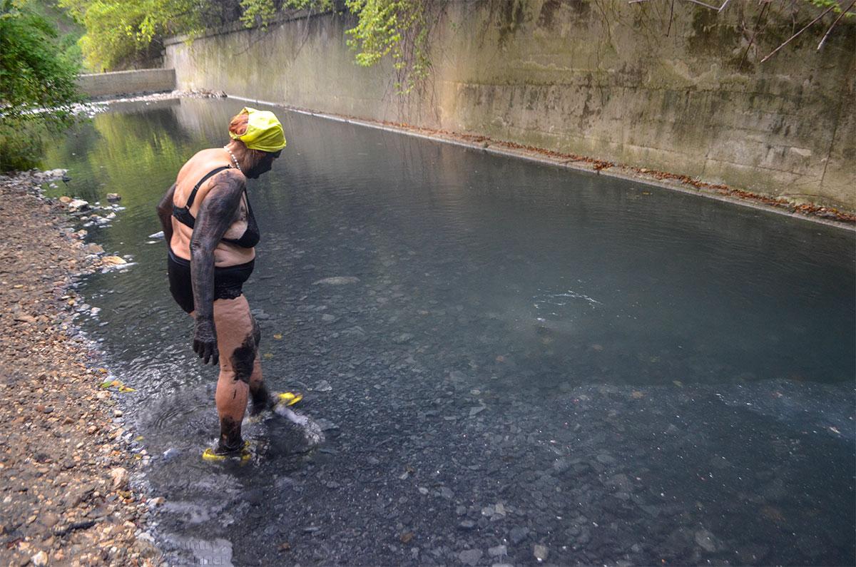 Исцеляющаяся гражданка направляется смывать грязь Агурских сероводородных источников к середине русла, где видны следы подземной струи.