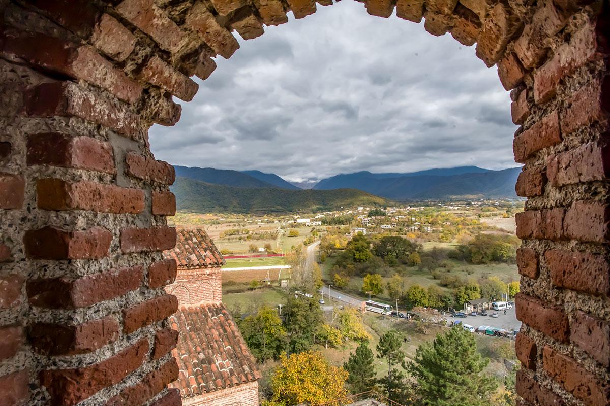 Исключительно живописные виды открываются через проем башни замка Греми, включая отроги Большого Кавказского хребта на горизонте.