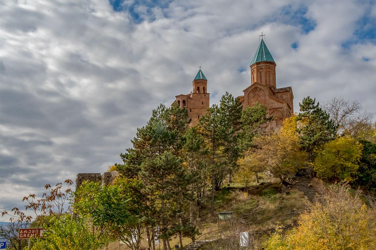 Замок Греми, по сути храмовый комплекс, обнесен каменной стеной, вписанной в гористый рельеф местности, с крепостными башнями при входе.