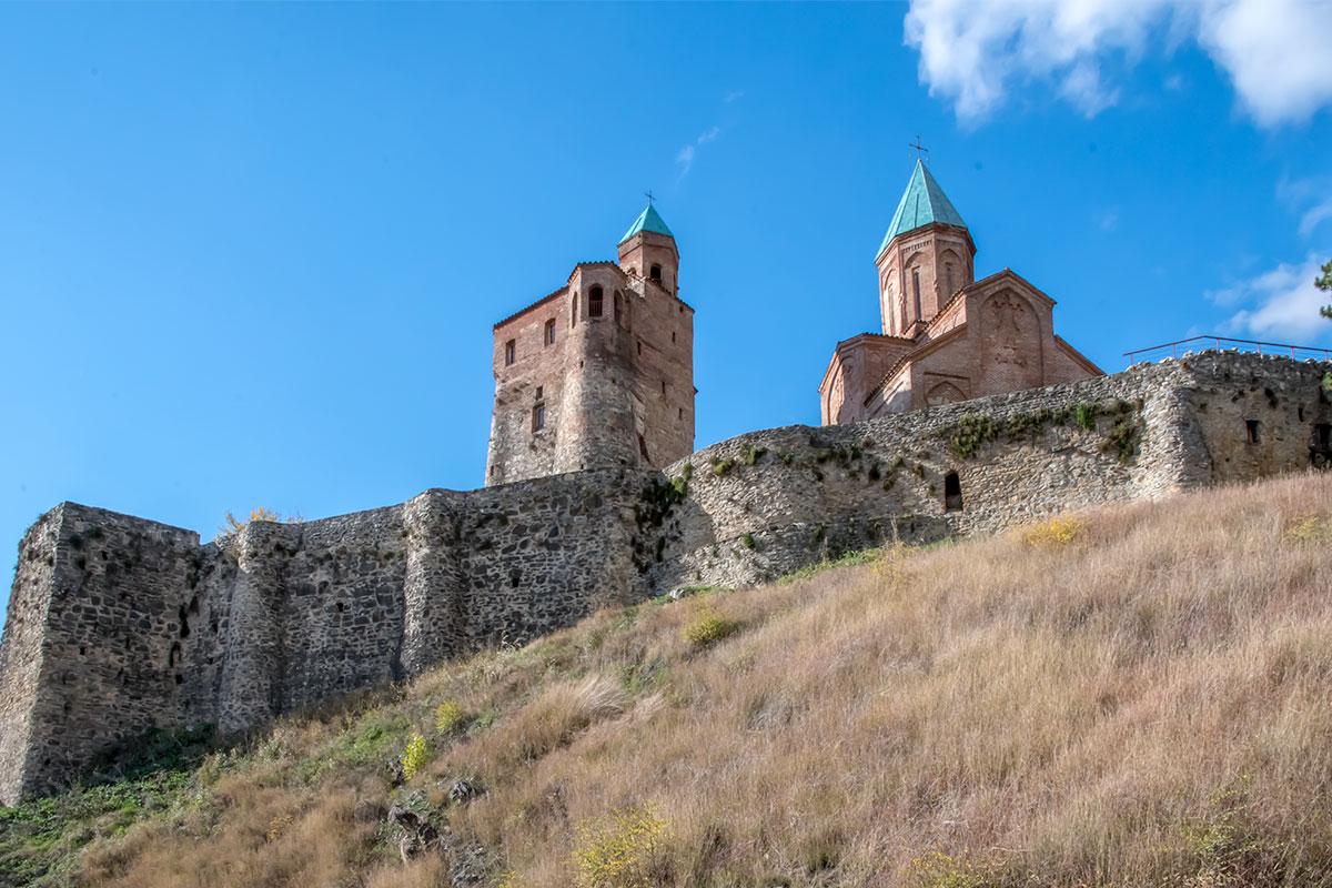 Выразительно выглядит замок Греми с юго-восточного направления, на переднем плане – каменная ограждающая стена.