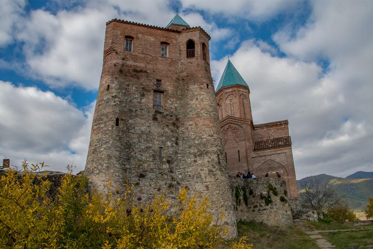 Составляющие замок Греми храм архангелов Михаила и Гавриила, а также жилая колокольня, соединяются крытым кирпичным переходом.