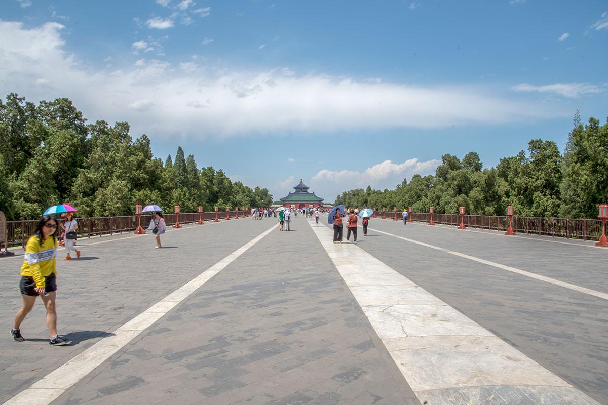 По мере удаления по Священной дороге Южные ворота сливаются со зданием с синей крышей, выступает и вершина башни Храма урожая.