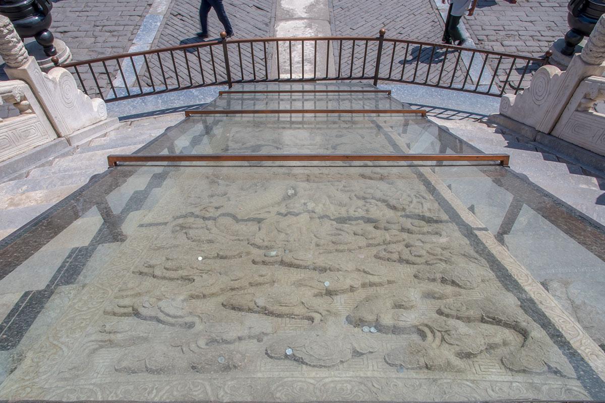 Бронированное стекло не защищает мраморную плиту на входе в Зал Небесного свода от преподносимых посетителями монеток.
