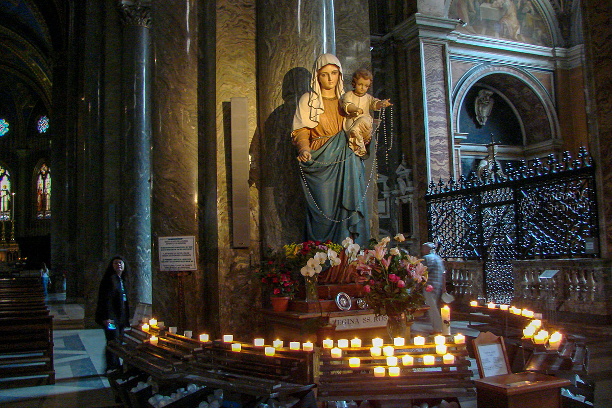 Богородица с младенцем, обязательный атрибут базилики Санта Мария сопра Минерва исходя из посвящения храма, оборудована вместительными подсвечниками.
