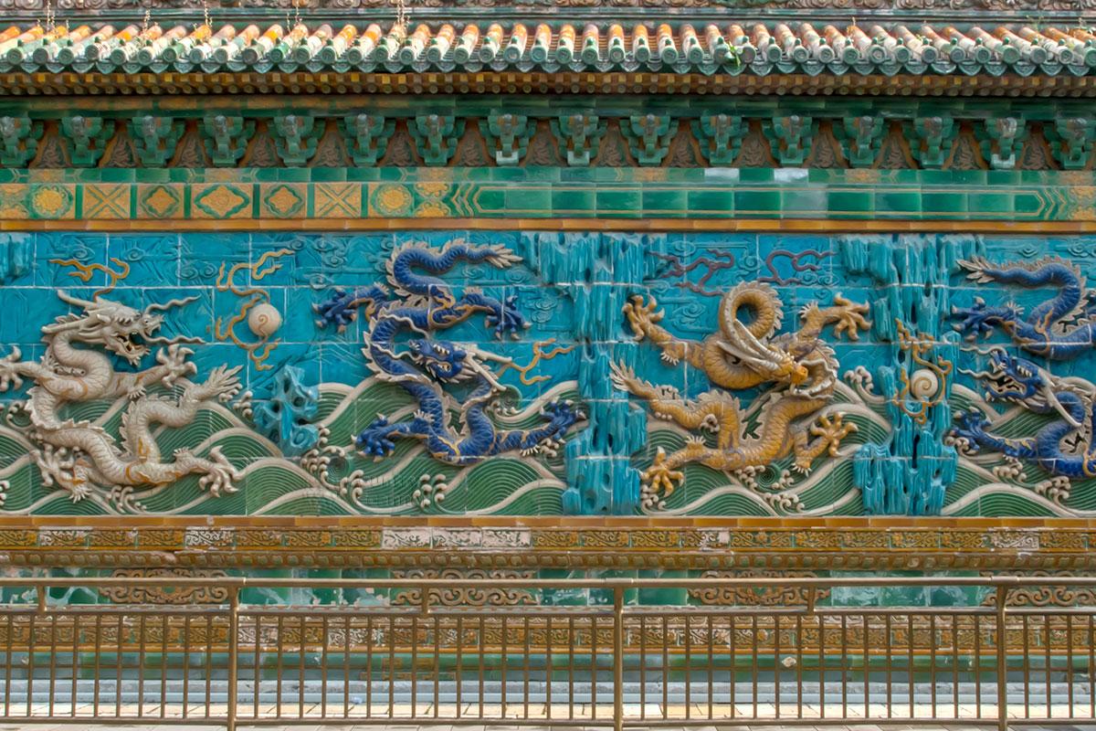 Яркостью цветов и живописностью персонажей Стена Девяти драконов парка Бэйхай восхищает публику.