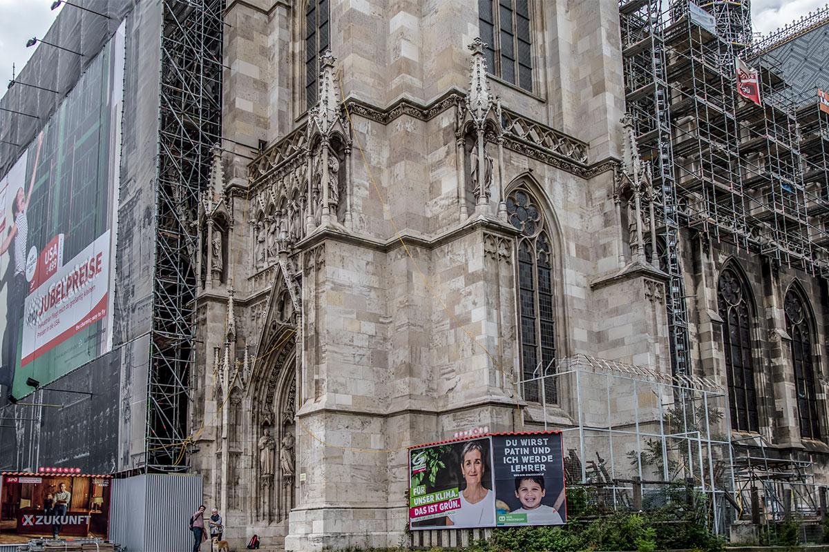 Центральный фасад Вотивкирхе с парными башнями большей частью закрыт плакатом, кроме входа, но скрыты за ним леса реставраторов.