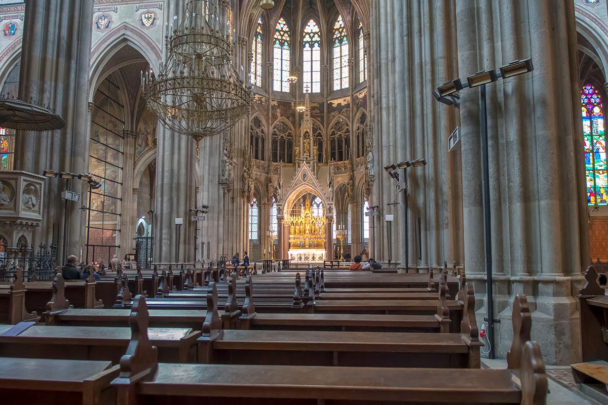 Традиционно для католических храмов, Вотивкирхе наполовину заставлена скамейками для прихожан, где не только сидят, но и молятся на коленях.