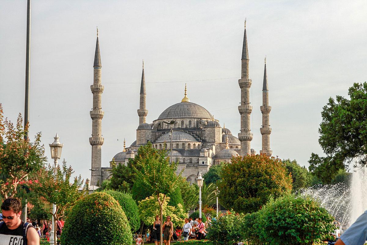 Живописный вид на Голубую мечеть открывается из парковой зоны площади Султанахмет, охватывая разнообразную растительность и красивое здание.