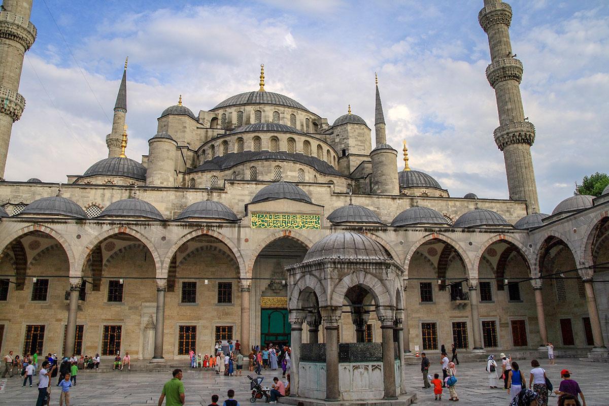 Внутренний двор стамбульской Голубой мечети постоянно заполнен народом, туристы ждут окончания молитвы либо прихожане пришли заранее.