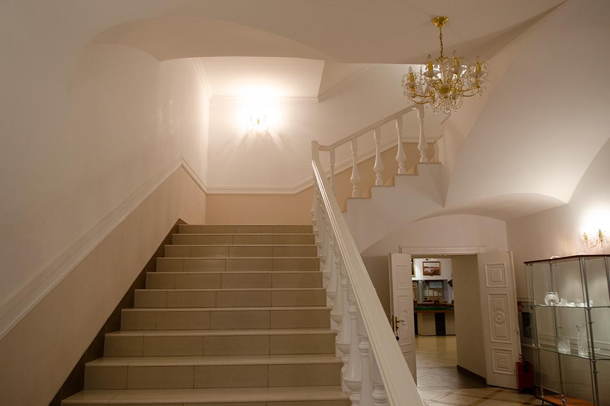 У основания лестницы на второй этаж Губернаторского дома в Пензе выставлена рекламная витрина выставки изделий из стекла и хрусталя.