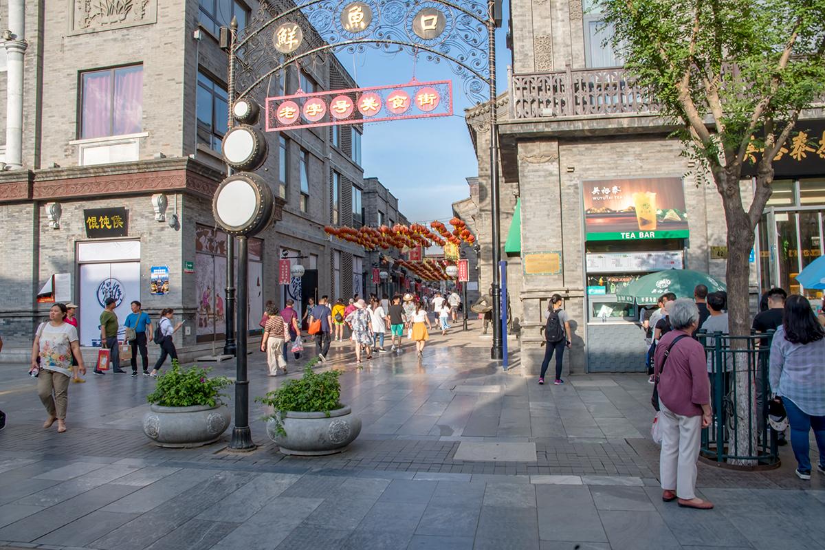 Проходы на перпендикулярные переулки с улицы Цяньмэнь украшены металлическими арками с разнообразными украшениями и иероглифами надписей.