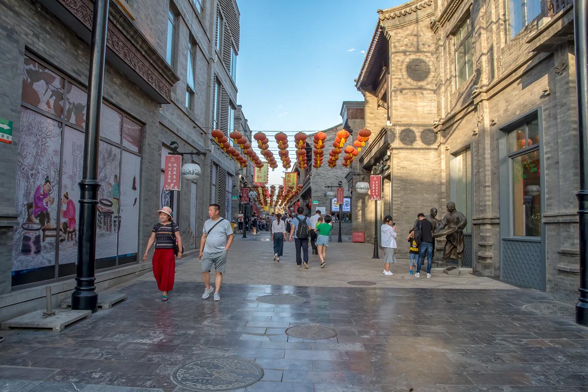 Вторично попадаем на улицу Цяньмэнь, пройдя под растяжками с фонариками и выйдя к магазину тканей, украшенному рисованной рекламой.