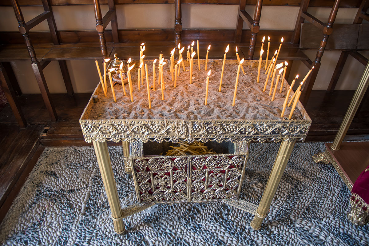 Отдельный кадр в обзоре монастыря Панагия Калопетра демонстрирует ажурный прямоугольный подсвечник, греки не делят свечи на поминальные и заздравные.