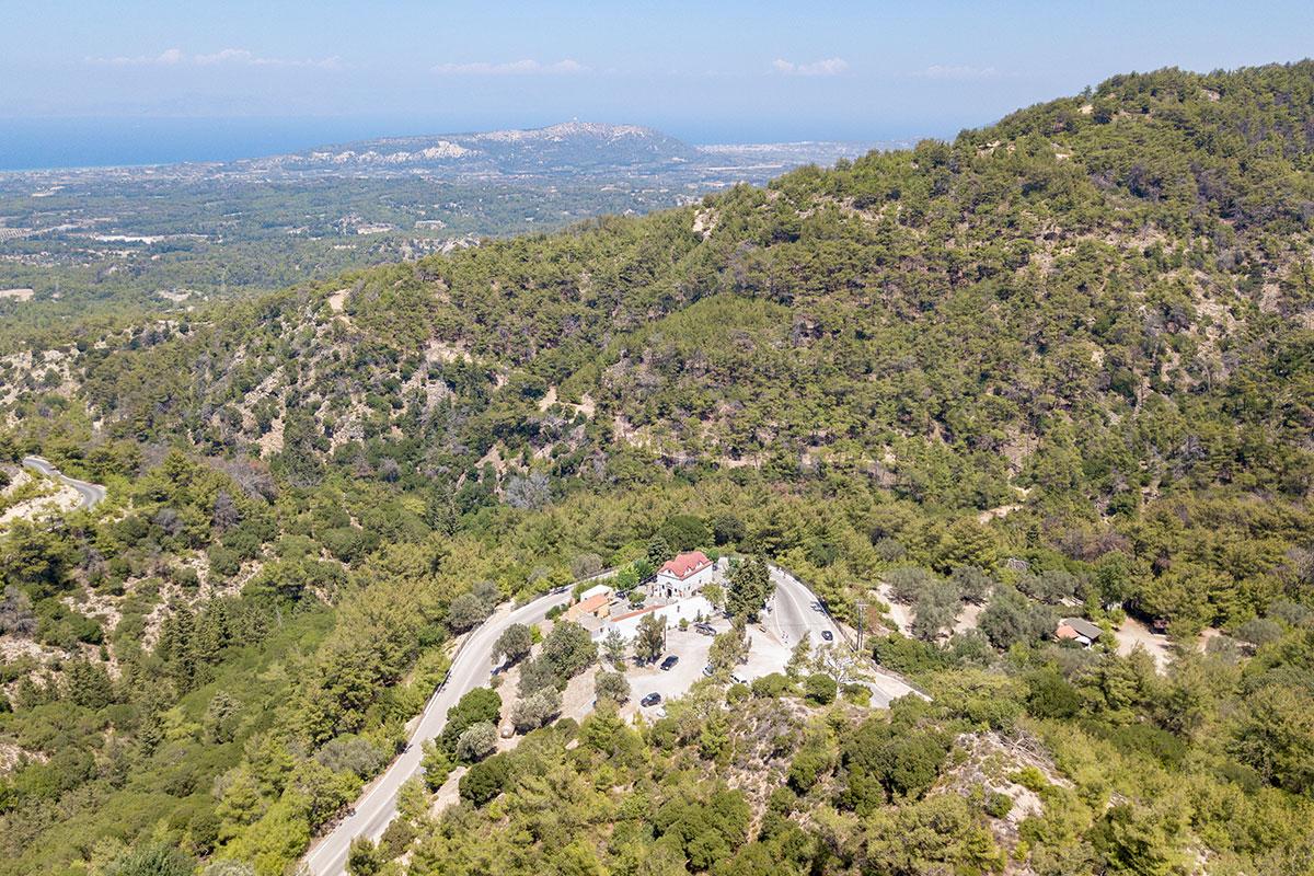На высотной фотографии монастырь Панагия Калопетра опоясан автомобильной дорогой, ведущей в местечко Петалудес, начало осмотра Долины бабочек.