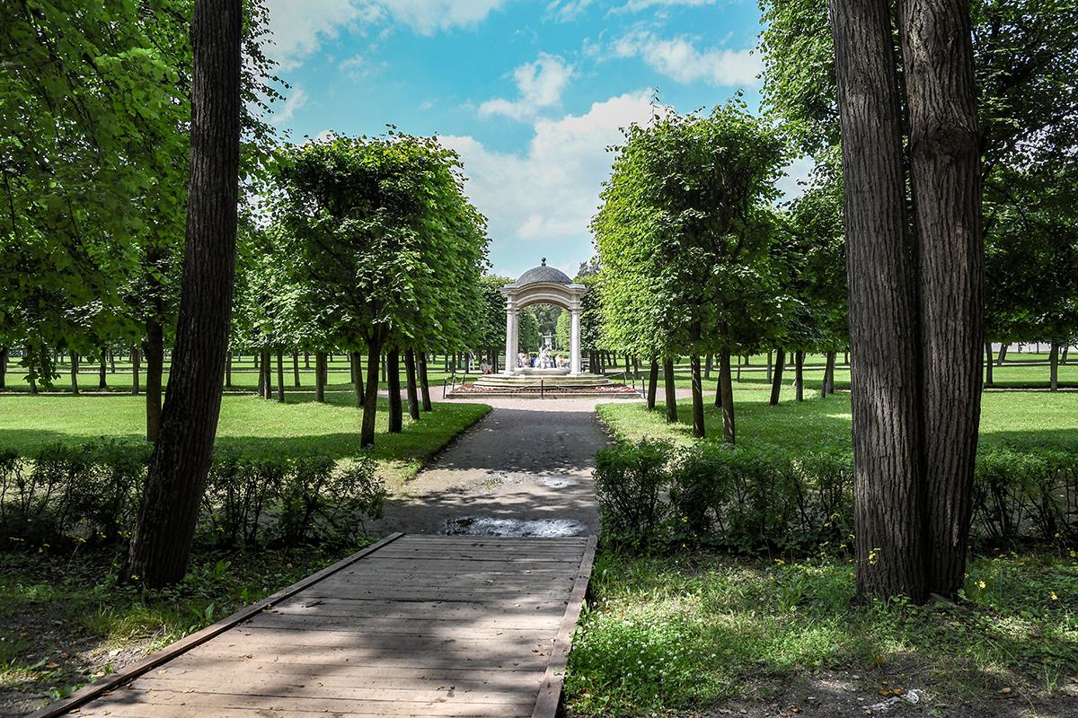 Оценивать совместимость розового фонтана со стриженными деревьями парка лучше с достаточного расстояния, когда видна перспектива.