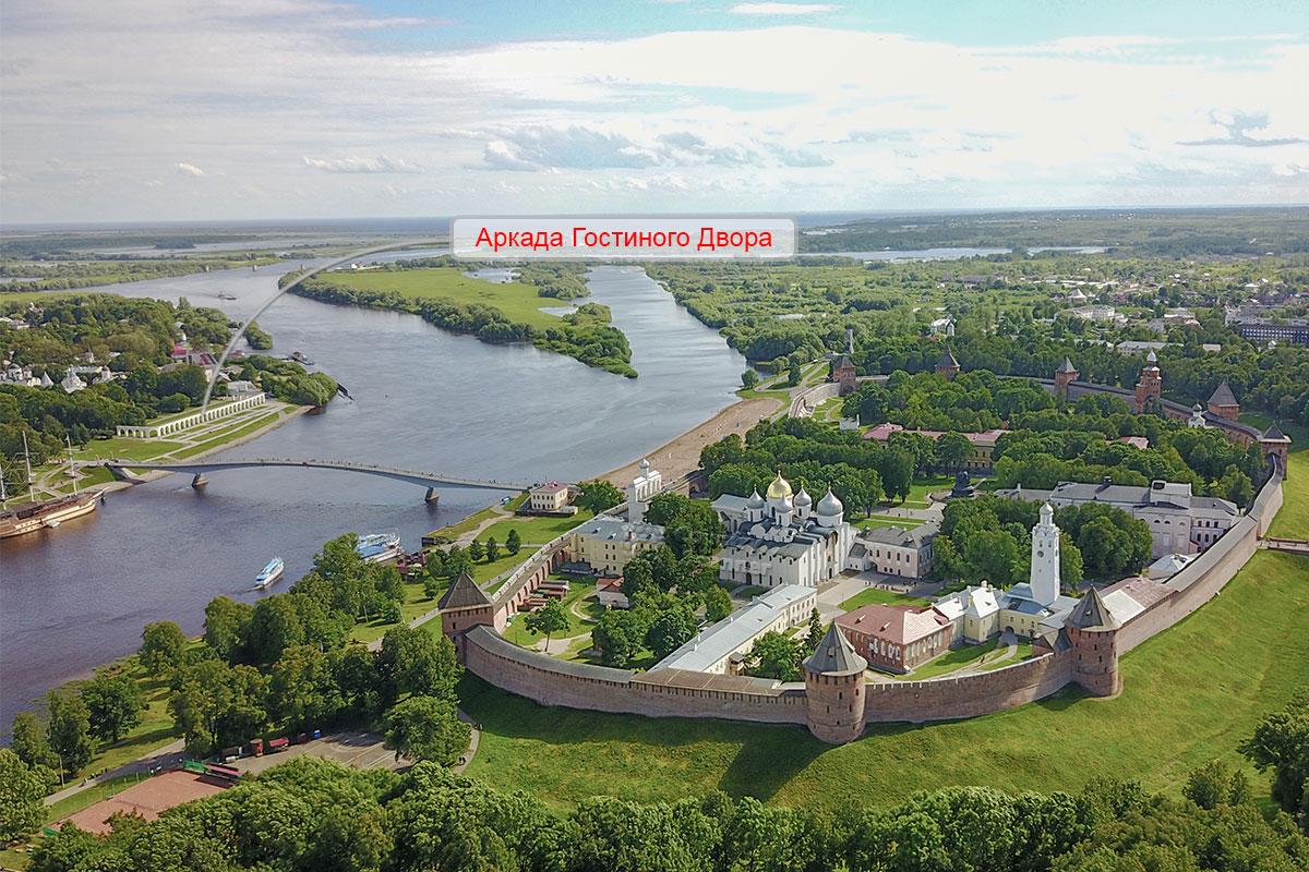 Панорамная высотная фотография отображает Новгородский кремль, русло Волхова с пешеходным мостом, на другом берегу – аркада Гостиного двора.
