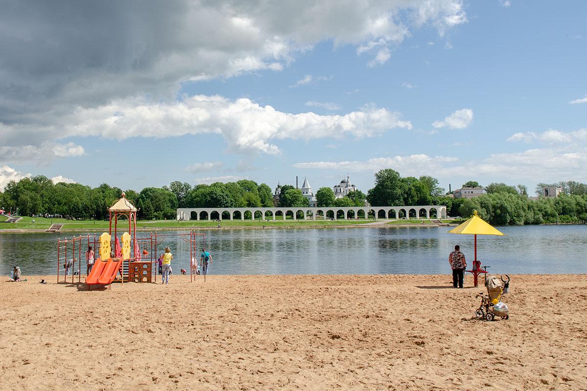 С территории песчаного пляжа под стенами Новгородского кремля на противоположном берегу хорошо видна аркада Гостиного двора и храмовые купола бывшего Торга.