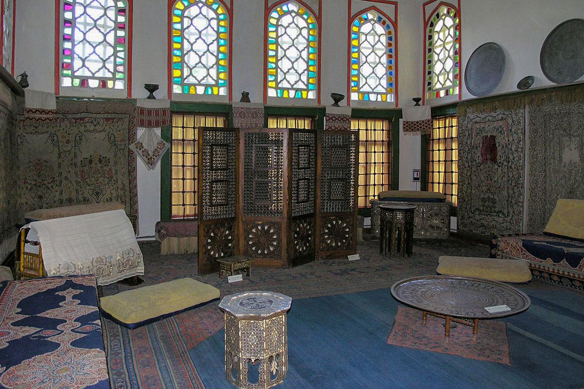 Помещение Буфетной в Гаремном корпусе Ханского дворца украшено витражными окнами, увешено коврами, большими металлическими блюдами.