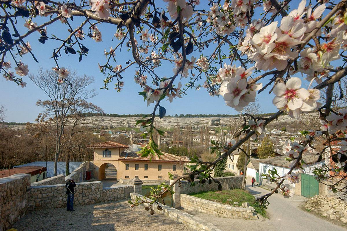 Весенняя панорама Ханского дворца с его южной окраины живописна за счет попавших в кадр распустившихся яблоневых цветков.