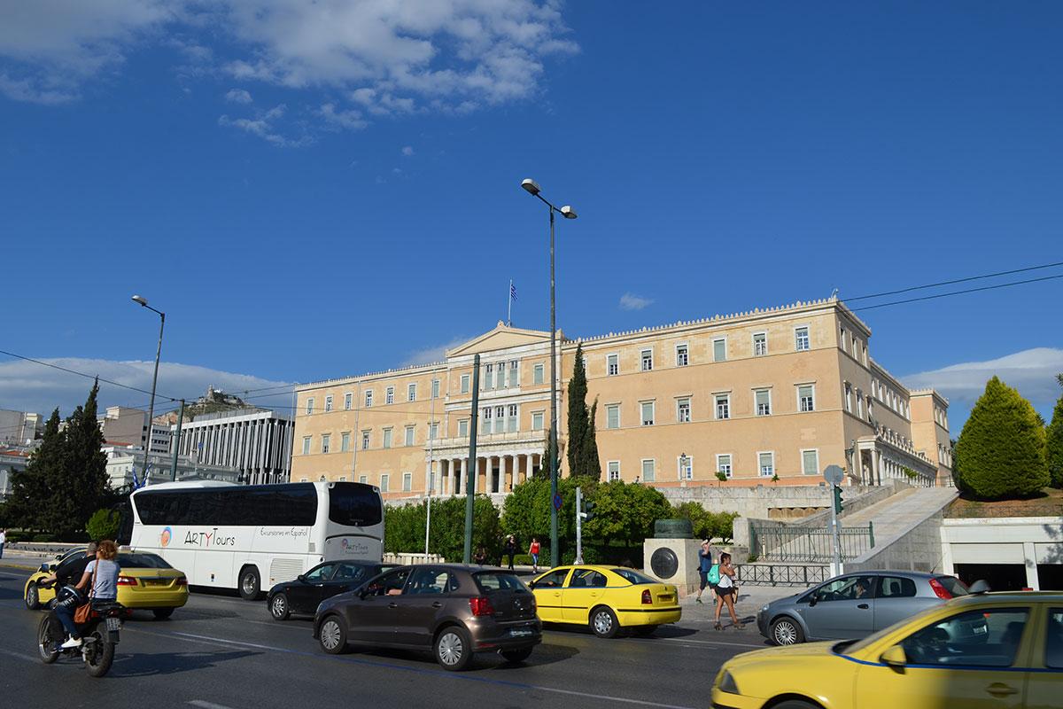 Западный фасад здания Парламента Афин соседствует с корпусами министерства иностранных дел, далее – вершина высочайшего холма города, Ликавиттос.