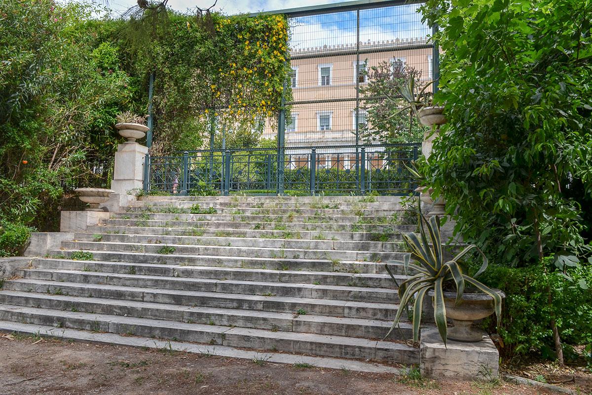 Ограждение здания Парламента Афин горазда более высокое и явно технически более сложное, чем металлическая ограда территории Национального сада.