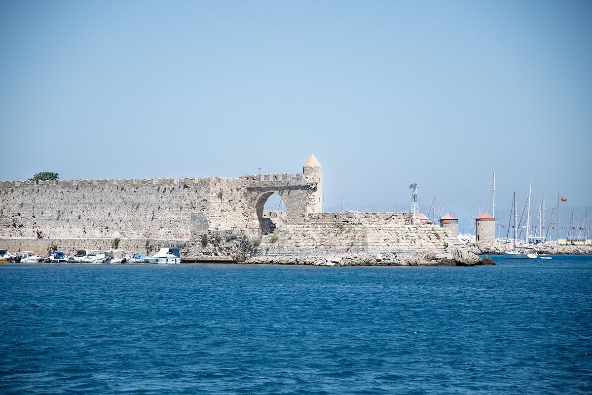 На фото из гавани Мандраки первым планом выступают укрепления форта Святого Николая, здесь ветряные мельницы Родоса обеспечивают фон.