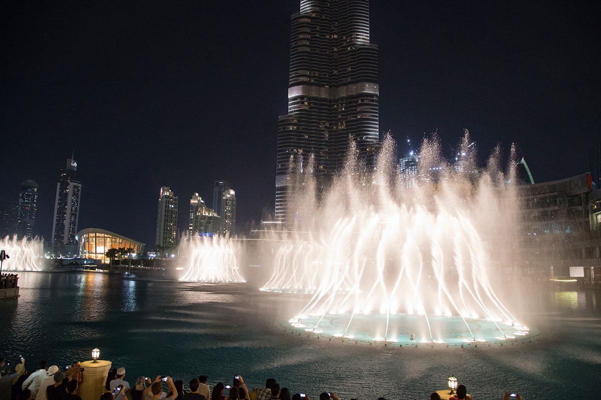 На фоне нижних ярусов высочайшего сооружения современности, Башни Халифа, впечатляюще выглядят костры из воды, огня и дыма фонтана Дубаи.