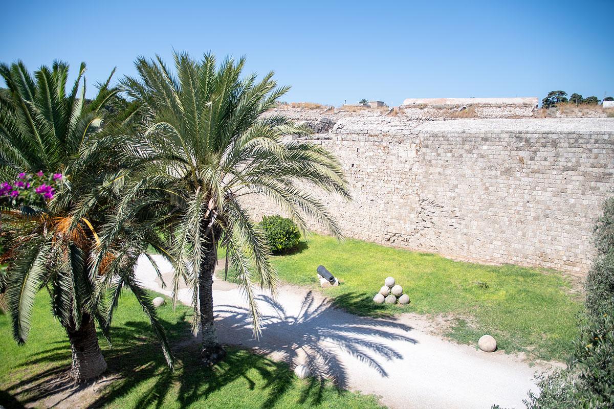 Дорожка вдоль южной крепостной стены Старого города Родоса, украшенная огромными ядрами и орудийными стволами, ведет к античному амфитеатру.