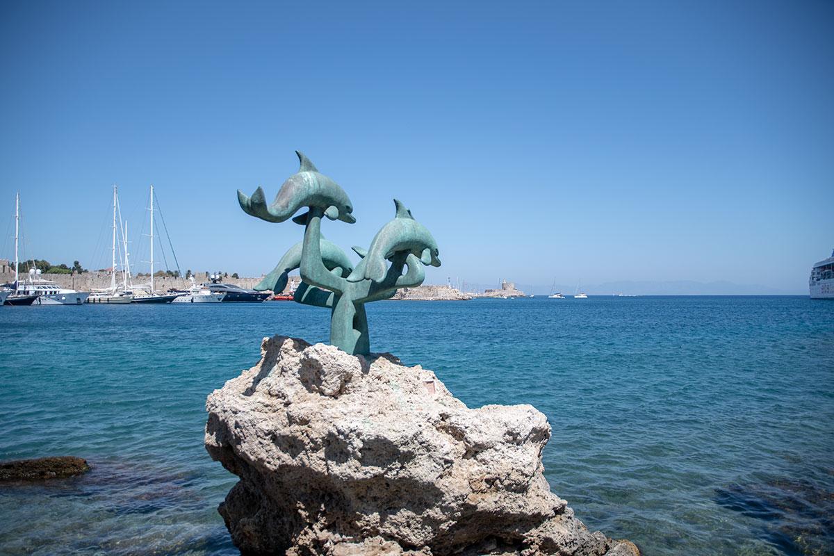Живописная скульптурная группа выпрыгивающих над водой дельфинов украшает набережную коммерческого порта вблизи входа в Старый город Родоса.