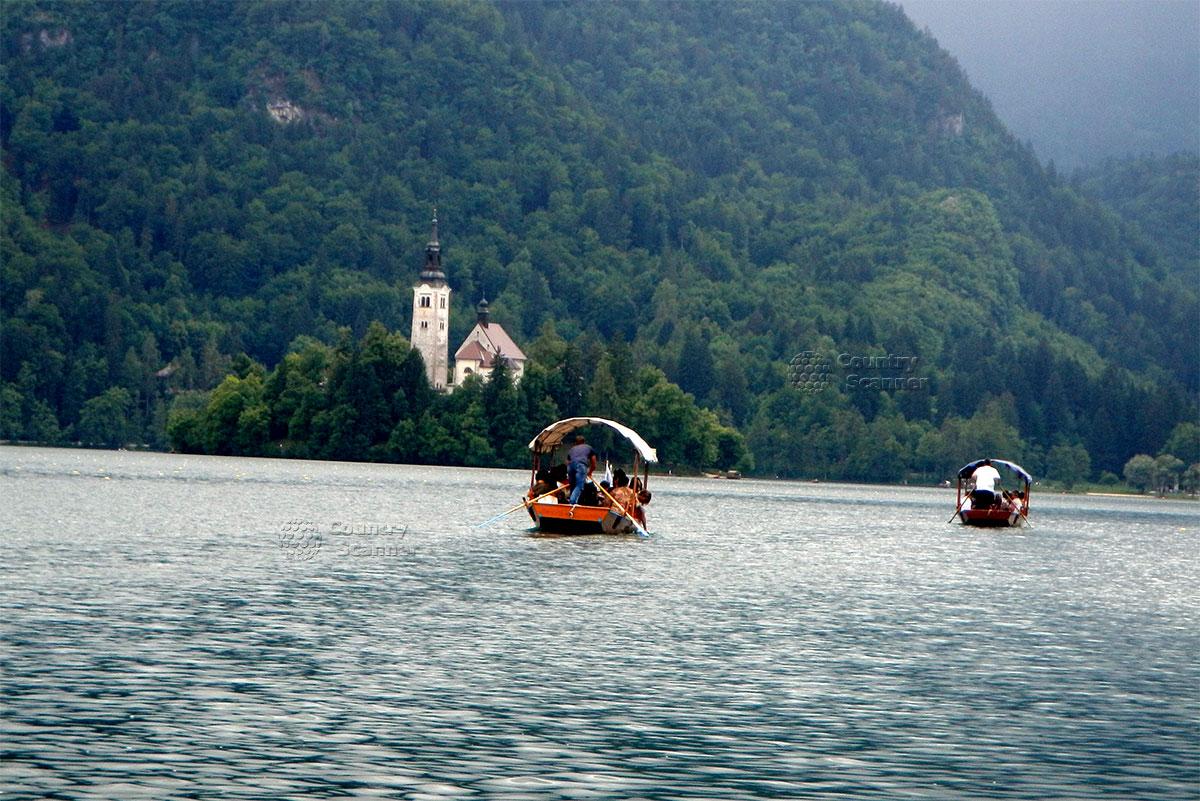 Две лодки с туристами плывут по озеру Блед