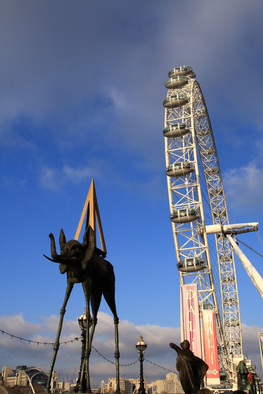 Памятник. Слон на длинных ногах на фоне Лондонского глаза.