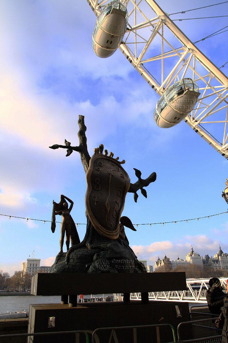 Памятник на фоне кабинок колеса обозрения Лондонский глаз в Лондоне.