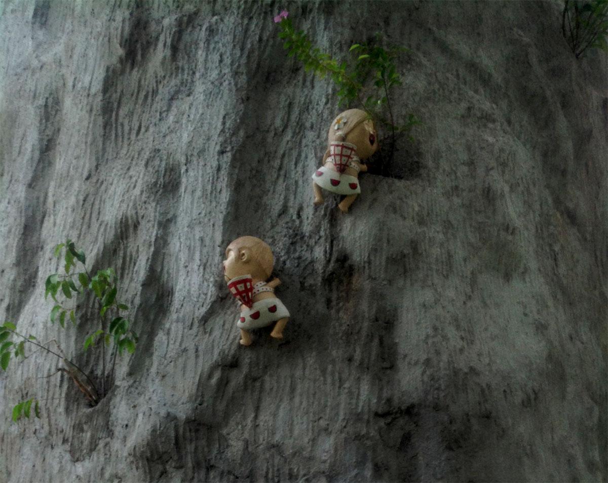 Минитюрные куклы парка Мини-Сиам, взбираются по импровизированному дереву