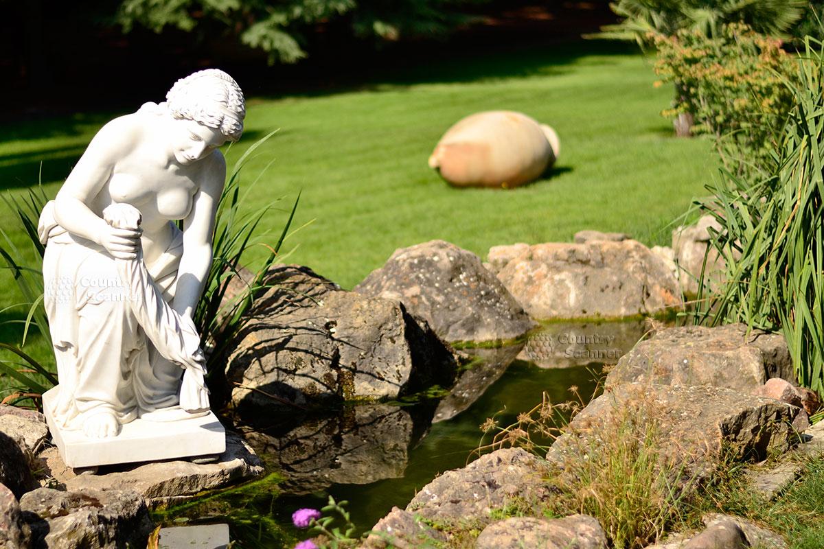 Мраморная статуя женщины, стирающей белье.