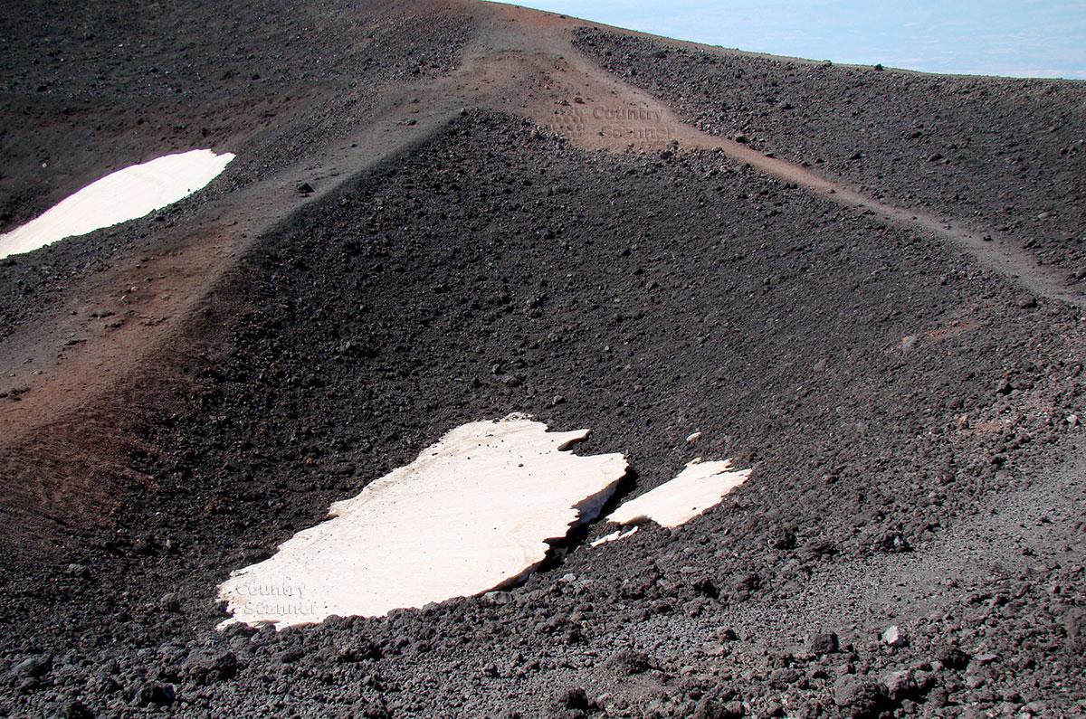 Склон вулкана Этна с участками снега.