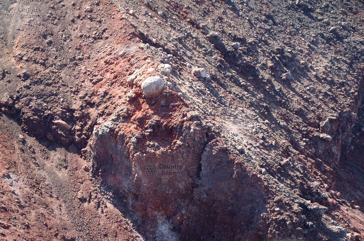 Поверхность склона вулкана Этна имеет, местами, оттенки красного цвета.