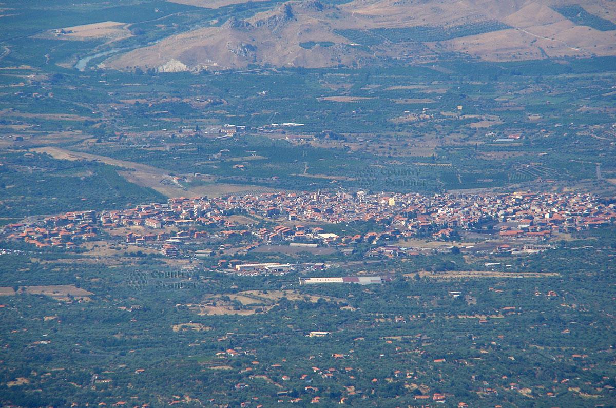 Вид населенных пунктов, находящихся неподалеку от вулкана Этна. Сильно увеличенное изображение, поэтому с дымкой.